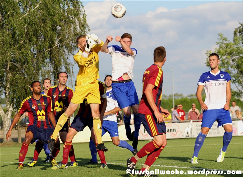 Kosuchowski (Nürnberg-Buch) klärt im Pokalspiel gegen die SpVgg Jahn Forchheim am 31. Juli mit beiden Fäusten vor einem Forchheimer Spieler.