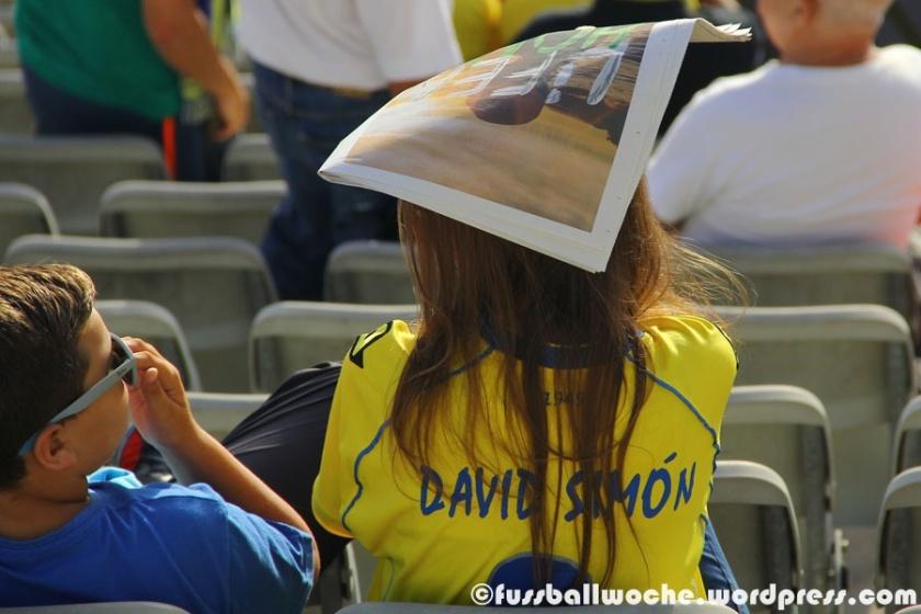 Eine Zuschauerin schützt sich mit der Stadionzeitung gegen die blendende Abendsonne (UD Las Palmas - Rayo Vallecano am 20.09.2015).